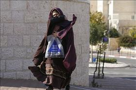 Haredi woman in Beit Shemesh wrapped in many layers of clothing and a veil. Photo: Michal Fattal, Flash 90